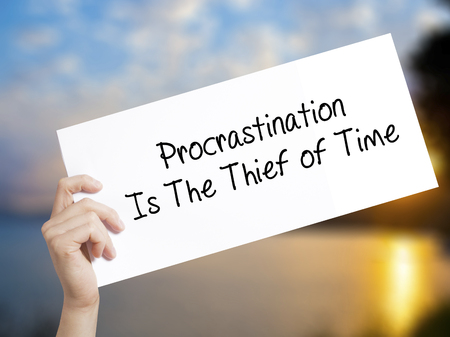 Procrastination Is The Thief of Time Sign on white paper. Man Hand Holding Paper with text. Isolated on sunset background.  Business concept. Stock Photo Stock Photo