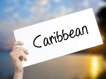 Caribbean Sign on white paper. Man Hand Holding Paper with text. Isolated on sunset background.   Business concept. Stock Photo Imagens