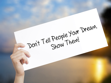 Dont Tell People Your Dream. Show Them! Sign on white paper. Man Hand Holding Paper with text. Isolated on sunset background.  technology, internet concept.