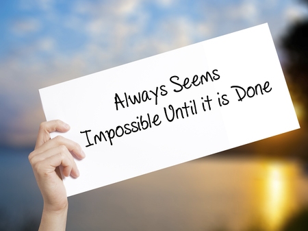 unachievable: Always Seems Impossible Until it is Done Sign on white paper. Man Hand Holding Paper with text. Isolated on sunset background.  Business concept. Stock Photo