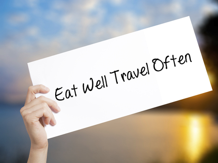 Eat Well Travel Often Sign on white paper. Man Hand Holding Paper with text. Isolated on sunset background.   Business concept. Stock Photo Stock Photo
