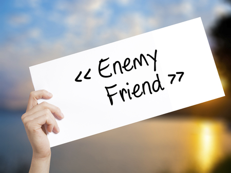 Enemy - Friend Sign on white paper. Man Hand Holding Paper with text. Isolated on sunset background.  Business concept. Stock Photo Stock Photo