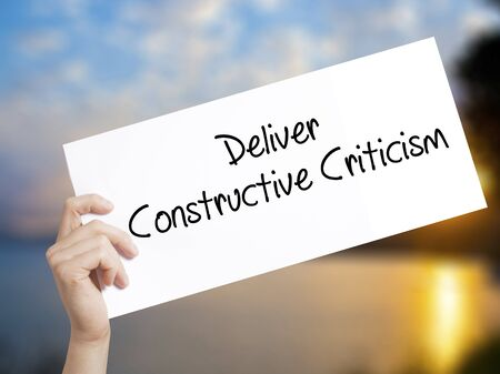 instability: Deliver Constructive Criticism Sign on white paper. Man Hand Holding Paper with text. Isolated on sunset background.  Business concept. Stock Photo Stock Photo