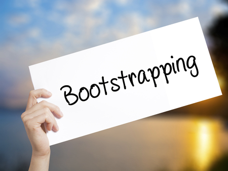 Bootstrapping Sign on white paper. Man Hand Holding Paper with text. Isolated on sunset background.  Business concept. Stock Photo Stock Photo