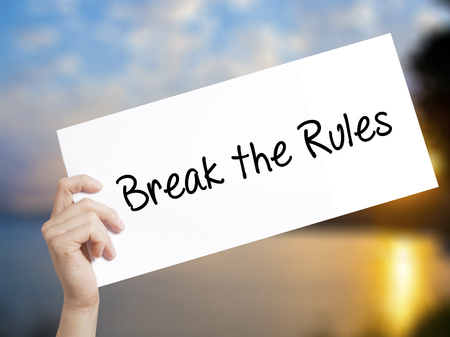 Break the Rules Sign on white paper. Man Hand Holding Paper with text. Isolated on sunset background.   Business concept. Stock Photo Stock Photo