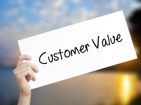 Customer Value Sign on white paper. Man Hand Holding Paper with text. Isolated on sunset background.  Business concept. Stock Photo Stock Photo - 77685561