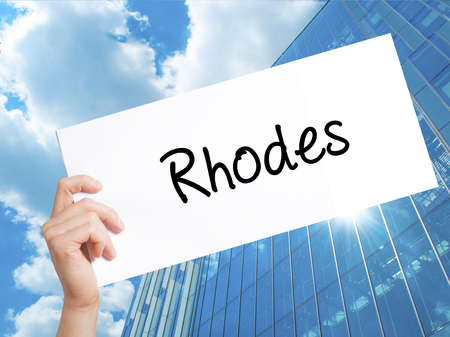 tsambika: Rhodes Sign on white paper. Man Hand Holding Paper with text. Isolated on Skyscraper background.   Business concept. Stock Photo Stock Photo