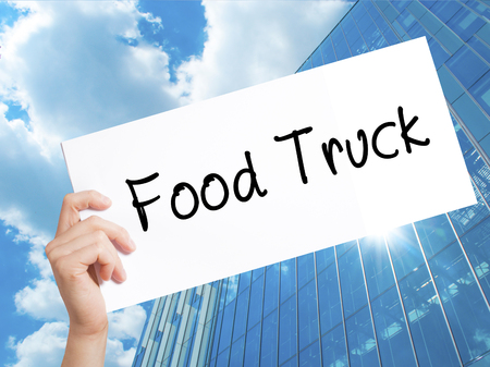 famous industries: Food Truck Sign on white paper. Man Hand Holding Paper with text. Isolated on Skyscraper background.  Business concept. Stock Photo Stock Photo