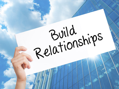 Build Relationships Sign on white paper. Man Hand Holding Paper with text. Isolated on Skyscraper background.  Business concept. Stock Photo