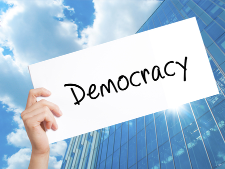 Democracy Sign on white paper. Man Hand Holding Paper with text. Isolated on Skyscraper background.  Business concept. Stock Photo Stock Photo