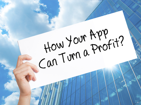 How Your App Can Turn a Profit? Sign on white paper. Man Hand Holding Paper with text. Isolated on Skyscraper background.  Business concept. Stock Photo