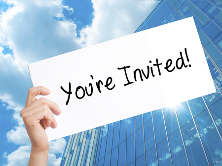 Youre Invited! Sign on white paper. Man Hand Holding Paper with text. Isolated on Skyscraper background.  Business concept. Stock Photo