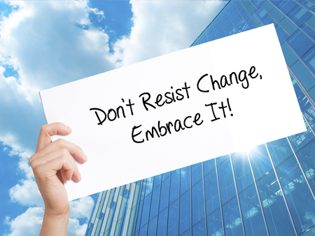 Dont Resist Change, Embrace It! Sign on white paper. Man Hand Holding Paper with text. Isolated on Skyscraper background.  technology, internet concept. Stock Photo