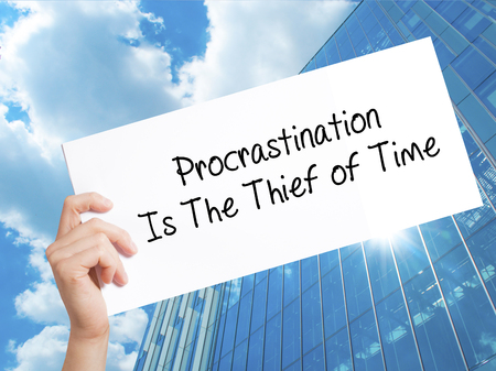 Procrastination Is The Thief of Time Sign on white paper. Man Hand Holding Paper with text. Isolated on Skyscraper background.  Business concept. Stock Photo Stock Photo