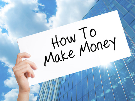 How To Make Money Sign on white paper. Man Hand Holding Paper with text. Isolated on Skyscraper background.  Business concept. Stock Photo