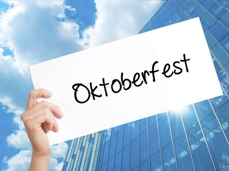 bier festival: Oktoberfest Sign on white paper. Man Hand Holding Paper with text. Isolated on Skyscraper background.   Business concept. Stock Photo