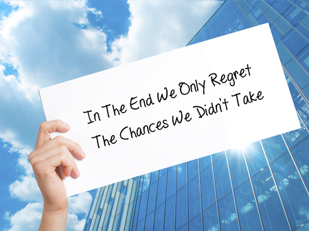 Paper with text In The End We Only Regret The Chances We Didnt Take . Man Hand Holding Sign on white paper. Isolated on Skyscraper background.   Business concept. Stock Photo