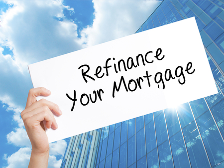 loaning: Refinance Your Mortgage Sign on white paper. Man Hand Holding Paper with text. Isolated on Skyscraper background.  Business concept. Stock Photo
