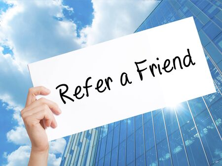 Refer a Friend  Sign on white paper. Man Hand Holding Paper with text. Isolated on Skyscraper background.  Business concept. Stock Photo