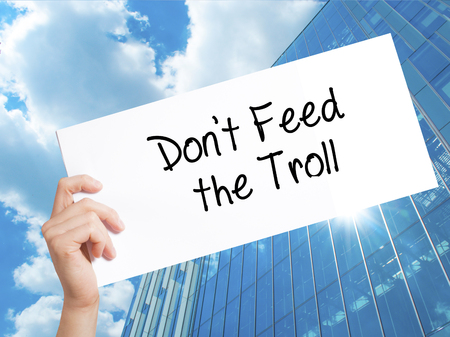 instigator: Dont Feed the Troll Sign on white paper. Man Hand Holding Paper with text. Isolated on Skyscraper background.  Business concept. Stock Photo