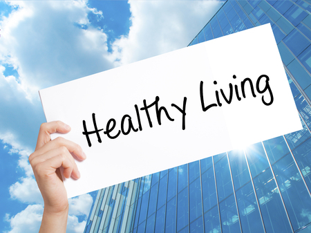 Healthy Living  Sign on white paper. Man Hand Holding Paper with text. Isolated on Skyscraper background.  Business concept. Stock Photo