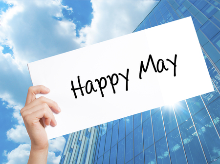 Happy May Sign on white paper. Man Hand Holding Paper with text. Isolated on Skyscraper background.   Business concept. Stock Photo Stock Photo