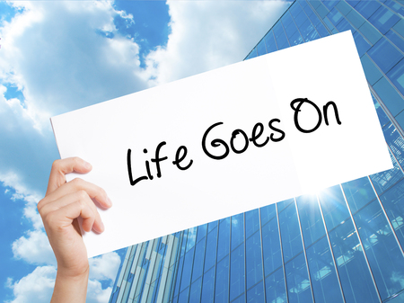 Life Goes On Sign on white paper. Man Hand Holding Paper with text. Isolated on Skyscraper background.   Business concept. Stock Photo