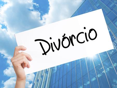 Divorcio (Divorcio en portugués) Firmar en papel blanco. Mano de hombre que sostiene el papel con el texto. Aislado en el fondo de rascacielos. Concepto de negocio. Foto de stock Foto de archivo - 77686457