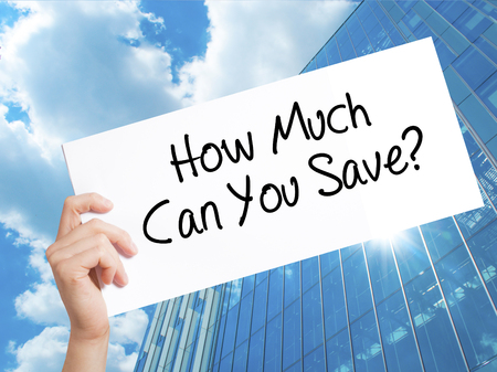 mortgaging: How Much Can You Save? Sign on white paper. Man Hand Holding Paper with text. Isolated on Skyscraper background.   Business concept. Stock Photo Stock Photo