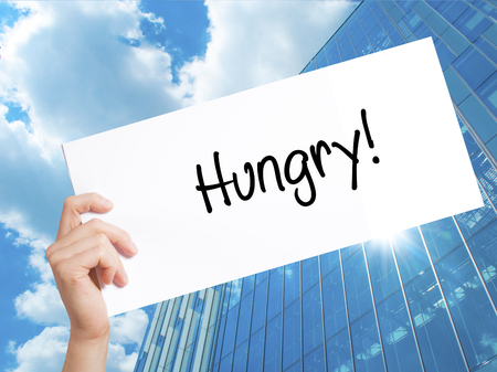 Hungry! Sign on white paper. Man Hand Holding Paper with text. Isolated on Skyscraper background.   Business concept. Stock Photo