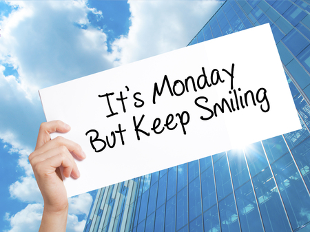 Its Monday But Keep Smiling Sign on white paper. Man Hand Holding Paper with text. Isolated on Skyscraper background.  Business concept. Stock Photo