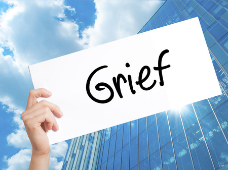 Grief Sign on white paper. Man Hand Holding Paper with text. Isolated on Skyscraper background.  Business concept. Stock Photo