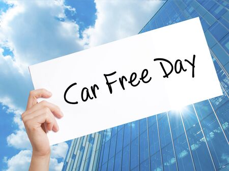 hand holding paper: Car Free Day Sign on white paper. Man Hand Holding Paper with text. Isolated on Skyscraper background.  Business concept. Stock Photo Stock Photo