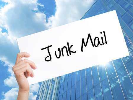 solicitors: Junk Mail Sign on white paper. Man Hand Holding Paper with text. Isolated on Skyscraper background.   Business concept. Stock Photo
