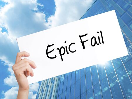 Epic Fail Sign on white paper. Man Hand Holding Paper with text. Isolated on Skyscraper background.  Business concept. Stock Photo