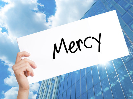 Mercy Sign on white paper. Man Hand Holding Paper with text. Isolated on Skyscraper background.   Business concept. Stock Photo