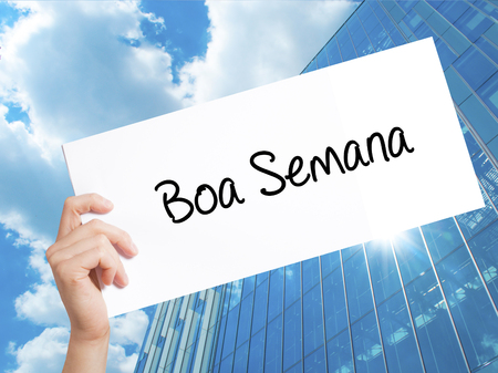 semana: Boa semana   (Good WeekIn portuguese)Sign on white paper. Man Hand Holding Paper with text. Isolated on Skyscraper background.   Business concept. Stock Photo