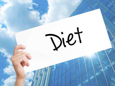nutricion: Diet (in Portuguese)  Sign on white paper. Man Hand Holding Paper with text. Isolated on Skyscraper background.   Business concept. Stock Photo