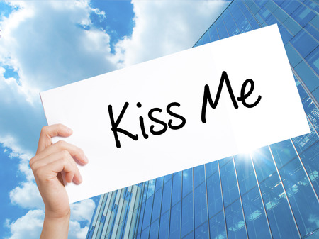Kiss Me Sign on white paper. Man Hand Holding Paper with text. Isolated on Skyscraper background.  Business concept. Stock Photo