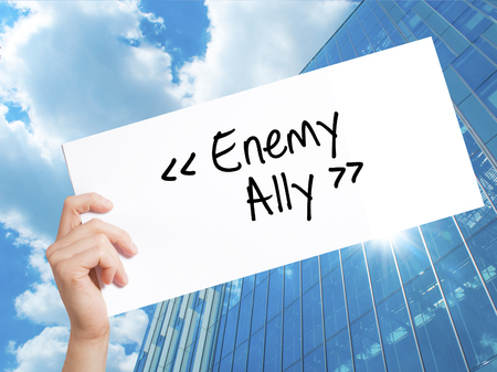 Enemy - Ally Sign on white paper. Man Hand Holding Paper with text. Isolated on Skyscraper background.  Business concept. Stock Photo
