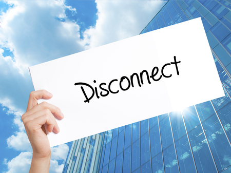disconnection: Disconnect Sign on white paper. Man Hand Holding Paper with text. Isolated on Skyscraper background.   Business concept. Stock Photo Stock Photo