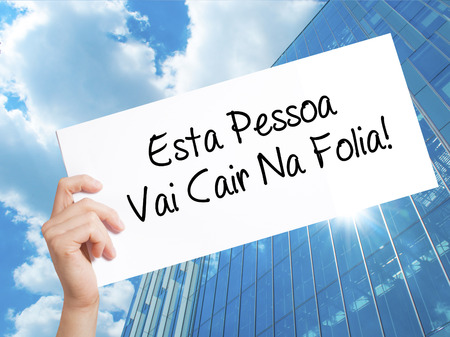 Esta Pessoa Vai Cair Na Folia! (This Person Will be at Carnaval in Portuguese) Sign on white paper. Man Hand Holding Paper with text. Isolated on Skyscraper background.  Business concept. Stock Photo Imagens