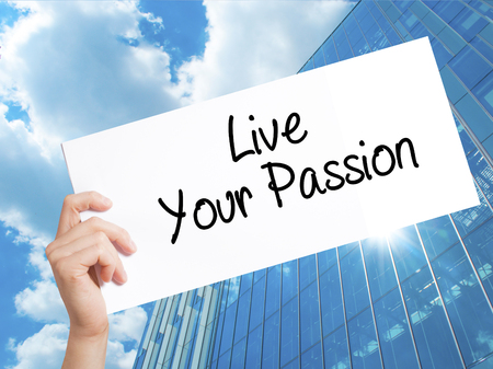 Live Your Passion Sign on white paper. Man Hand Holding Paper with text. Isolated on Skyscraper background.   Business concept. Stock Photo