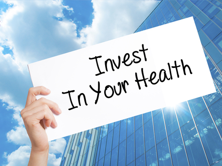 Invest In Your Health Sign on white paper. Man Hand Holding Paper with text. Isolated on Skyscraper background.  Business concept. Stock Photo Stock Photo