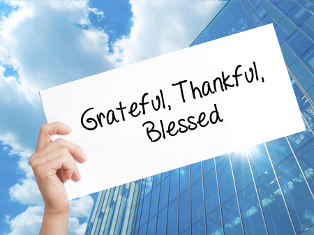 humility: Grateful Thankful Blessed Sign on white paper. Man Hand Holding Paper with text. Isolated on Skyscraper background.  Business concept. Stock Photo