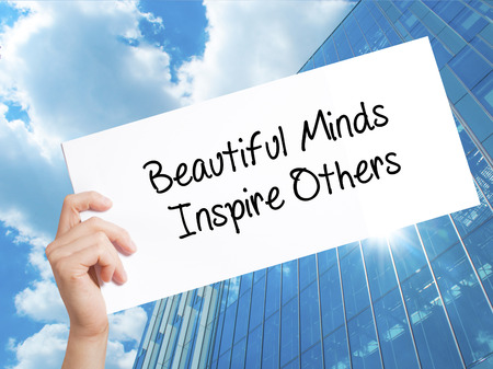 spiritual energy: Beautiful Minds Inspire Others Sign on white paper. Man Hand Holding Paper with text. Isolated on Skyscraper background.   Business concept. Stock Photo