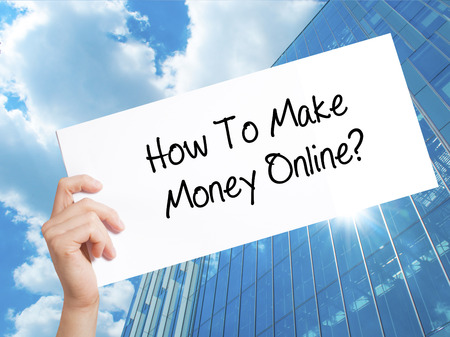 How To Make Money Online? Sign on white paper. Man Hand Holding Paper with text. Isolated on Skyscraper background.  Business concept. Stock Photo