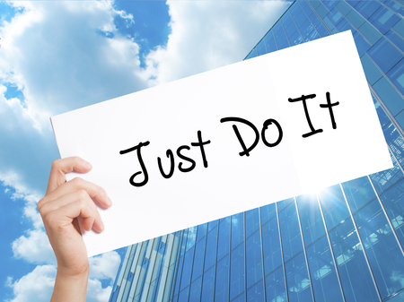 Just Do It Sign on white paper. Man Hand Holding Paper with text. Isolated on Skyscraper background.   Business concept. Stock Photo