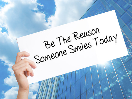Be The Reason Someone Smiles Today  Sign on white paper. Man Hand Holding Paper with text. Isolated on Skyscraper background.   Business concept. Stock Photo Фото со стока