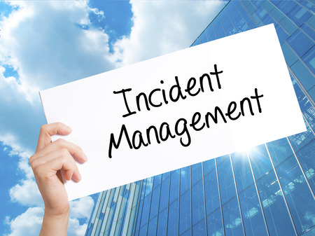 iscp: Incident Management Sign on white paper. Man Hand Holding Paper with text. Isolated on Skyscraper background.   Business concept. Stock Photo